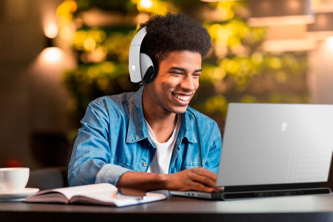 Estudiante que usa el Alienware m15 R4 mientras escucha música